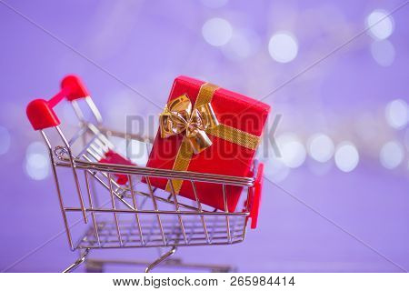 red gift box in small supermarket trolley with garland lights on purple bokeh background new year banner with empty space concept of valentine day