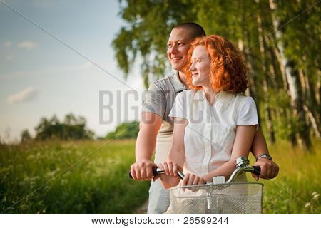 Young couple sitting one bicycle and looking at something