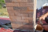 Installing house chimney blocks on the rooftop. Roofer decorate and protecting chimney bricklaing. poster