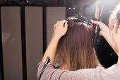 professional hairdresser clipping hair of a young model with a hairpin before making a beautiful coiffure in a beauty salon poster