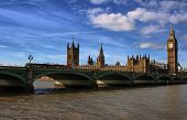 The Big Ben,the Houses of Parliament and Westminster bridge in London in a clear day with a dramatic looking sky poster