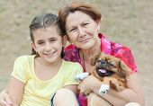 Adorable latin girl, her grandmother and the family dog in a park poster