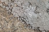 Surface of cracked and damaged outdoors cement-sand mortar leveling screed on concrete. Atmospheric harmful effects on unprotected construction. poster