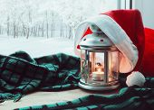 Festive tranquil Christmas and New Year still life -lantern with candle and Christmas Santa hat on the windowsill and winter park outdoor. Concept of Christmas and New Year.Christmas and New year still life. Christmas composition poster