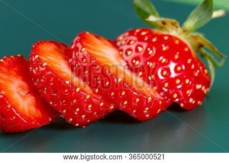 Fruit Background. Several Slices Of Strawberries On A Green Background. Texture Of Strawberries. Clo
