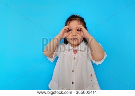 A Cute Young Asian Girl Is Pretending To Be A Spy, Using Her Hands As Her Pretend Binoculars, Playin