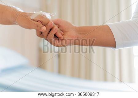 Caregiver Of Specialized Assistance With Care Hands Holding Hand Woman In Hospice Care, Philanthropy