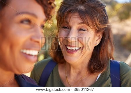 Two Senior Female Friends Hiking Along Trail In Countryside Together