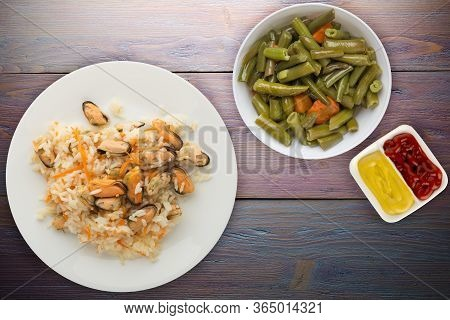 Rice With Mussels And Carrots On A White Plate. Rice With Mussels And Carrots On A Purple Wooden Bac