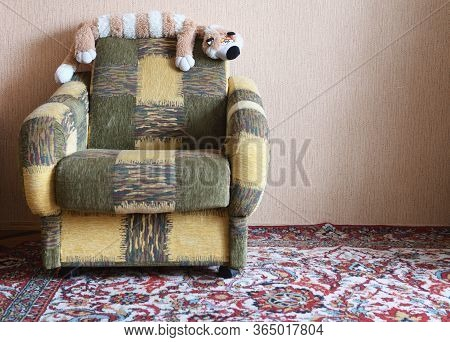 Upholstered Furniture Armchair With A Toy Cat And A Carpet On The Floor In A Soviet Apartment, Inter