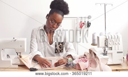 Attractive African-american Female Fashion Designer Sews Fashionable Clothes In Her Workshop. Africa