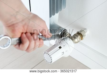 Worker Hands Repairing Radiator With Wrench. Close-up.removing Air From The Radiator And Fixing A He