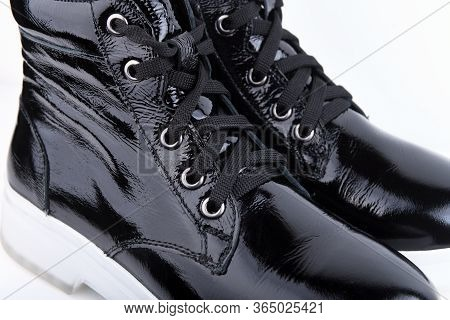 Female Boot From Black Patent Leather On A White Sole, On A White Background Close-up. Elegant Leath