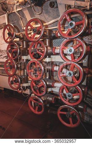 Many Round Cranes For Closing Valves On A Ship. Red Hilt. Horizontal.