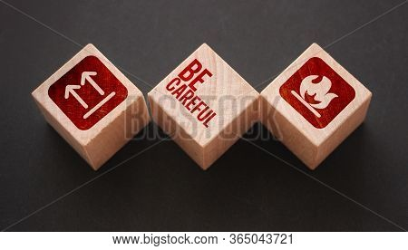 Wooden Cubes With The Text: Be Carefull And Icons Meaning Flamable And No Turing Upside Down. Beware