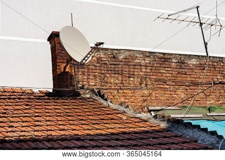 Satellite And Analogue Television Antennas On The Vintage Roof Tiles