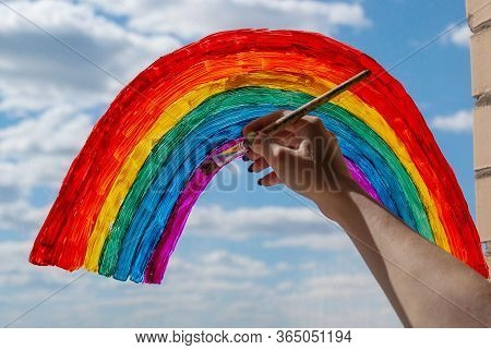 A Young Girl Draws A Rainbow On The Window Glass With A Brush And Gouache Against A Blue Sky With Wh