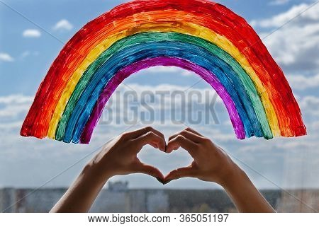 A Young Girl Made A Heart Sign With Her Hands Against The Background Of A Painted Rainbow On The Win