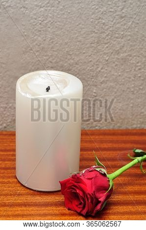 A White Candle With A Red Rose