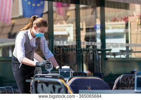Vilnius, Lithuania - April 30 2020: Waitress With A Mask Disinfects The Table Of An Outdoor Bar, Caf