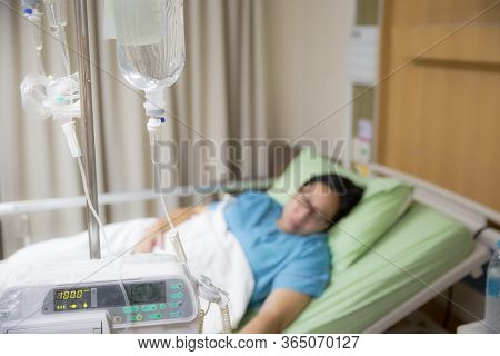 Focus The Hanging Saline Solution  With Blur Patient Background.illness And Treatment. Health Insura