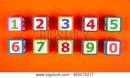 Wooden Cubes With Numbers Exactly Stacked On An Orange Background Top View Close-up Developing A Toy
