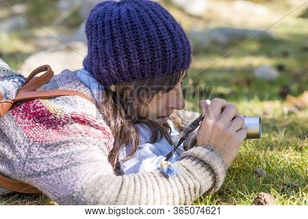 Woman With Wool Cap Lying On The Forest Ground While Taking A Photograph