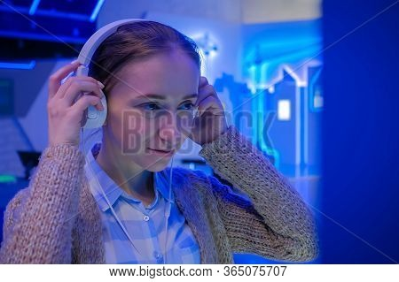 Woman Looking At Exposition, Using White Headphones And Listening Audio Guide At Modern Futuristic E