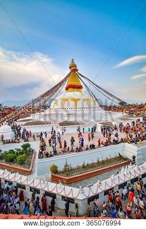 Kathmandu, Nepal - June 30 2019: Crowd Of Buddhist Devotees Circulating The Holy Boudhanath Stupa On