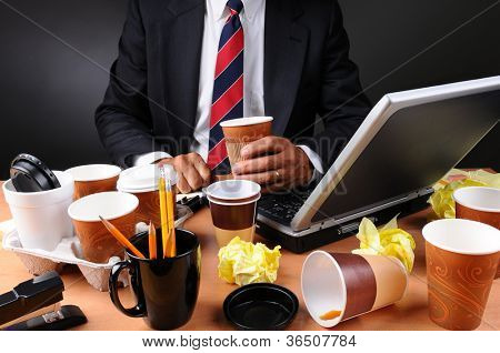 Closeup view of a very cluttered businessmans desk. Man is holding a coffee cup and crumpled papers litter his workspace. Horizontal format on a light to dark gray background.