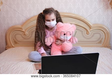A Girl In A Face Mask With A Pink Teddy Bear In A Face Mask Looks At A Laptop While Sitting On The B