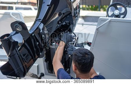 Mechanic Is Installing Speed Boat Engine , A New Engine On An Aluminum Boat.