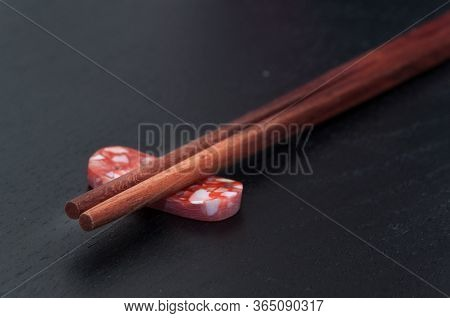 Wooden Chopsticks Rest On Colorful Stone With Dark Background. Close Up.