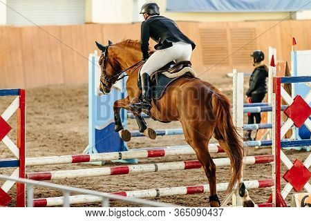 Equestrianism On Horse Jump Over Obstacle In Competition