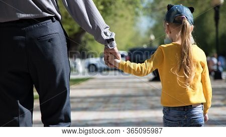 A Child Walks With His Father On The Street In The Park. A Man Holds The Hand Of A Child In A Mask F