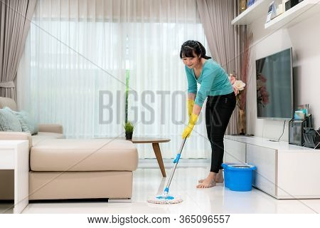 Attractive Young Asian Woman Mopping Tile Floor At Living Room While Doing Cleaning At Home During S