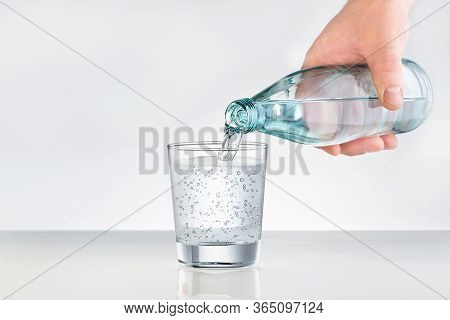 Male Hands Pouring Bottled Water Into Glass. Water Glass With Copy Space. Mineral Water For Healthy