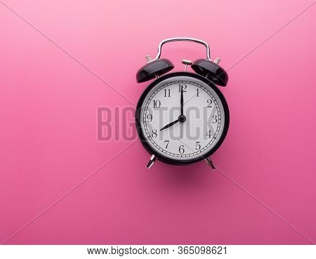 Black Retro Alarm Clock On Pink Background With Copy Space Isolated Pointing Eight O Clock. Black Vi