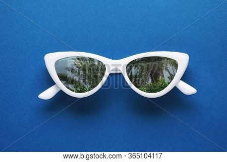 Stylish Sunglasses With Reflection Of Palm Trees On Blue Background, Top View