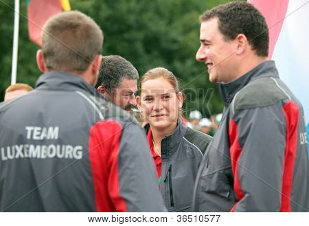 RAUBICHI, BELARUS - AUGUST 24: Sarah Kandel from Luxembourg, the unique female logger among her teammates during World Logging Championship in Raubichi, Minsk region, Belarus at August 24, 2012