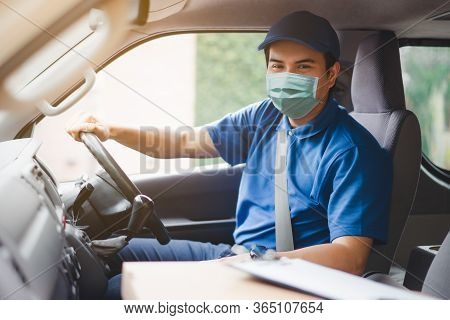 Young Asian Delivery Man Wearing Protective Face Mask Driving His Van With Packages On The Front Sea
