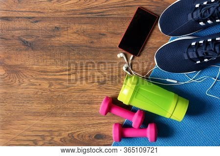 Fitness Equipment Top View With Copy Space. Dumbbells, Water Bottle, Sport Shoes And Fitness Mat On