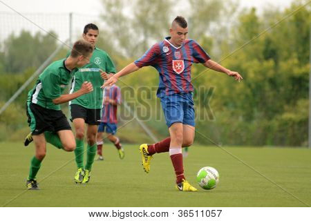 KAPOSVAR, HUNGARY - SEPTEMBER 1: Unidentified players in action at the Hungarian National Championship under 18 game between Kaposvar(green) and Videoton (blue) September 1, 2012 in Kaposvar, Hungary.