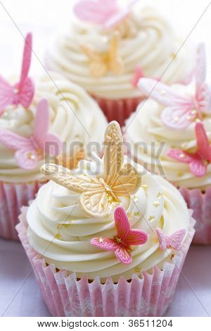 Cupcakes decorated with pink and gold fondant butterflies