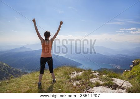 Joyful girl standing on mountain top with raised arms looking at mountain landscape and blue sky.