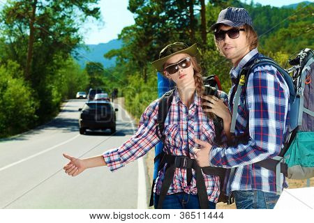 Two young people tourists hitchhiking along a road.