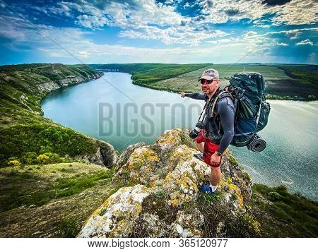 Bacota, Ukraine 29.04.2020 Man With Backpack On A Top Of Rock Ower Beautiful Canyon River Landscape.