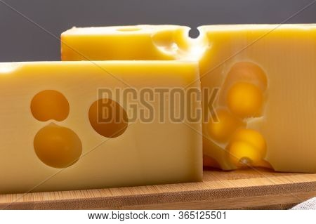 Block Of Swiss Medium-hard Yellow Cheese Emmental Or Emmentaler With Round Holes Close Up