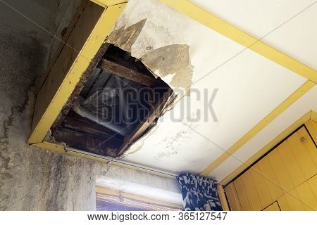 Water Damaged Ceiling In An Old Abandoned House.broken Damaged Ceiling With Hole