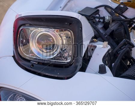 Close Up Of Pop-up Headlight On White Car